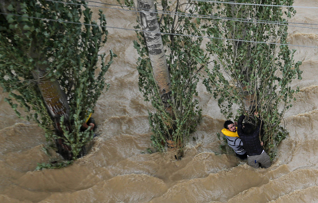 . Kashmiris hang on to a tree to prevent being swept away by floodwaters in Srinagar, India, Tuesday, Sept. 9, 2014.  The flooding began earlier this month in Kashmir, where it has caused landslides and submerged much of the main city of Srinagar, on the Indian-administered side. (AP Photo/Dar Yasin)