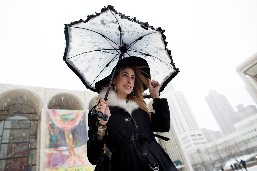 . Lauren Rae Levy, of Manhattan, stands outside the Metropolitan Opera House in the snow at Lincoln Center during Fashion Week, Friday, Feb. 8, 2013, in New York. Snow began falling across the Northeast on Friday, ushering in what was predicted to be a huge, possibly historic blizzard and sending residents scurrying to stock up on food and gas up their cars. (AP Photo/John Minchillo)