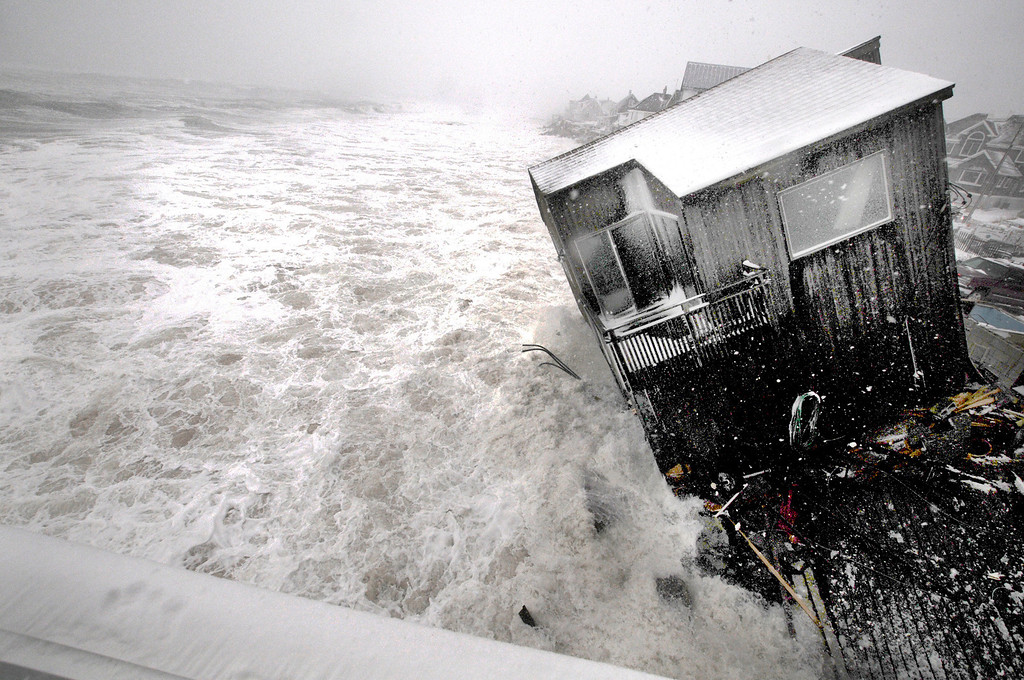 . A house on the Plum Island seacoast in Newbury, Mass., sits partially collapsed into the churning surf, driven by winds from a slow-moving storm centered far out in the Atlantic Ocean, at high tide Friday morning, March 8, 2013. The storm dropped up to a foot of snow in some parts of New England, caused coastal flooding in Massachusetts and slowed the morning commute in the region to a slushy crawl.  (AP Photo/Newburyport Daily News, Jim Vaiknoras)