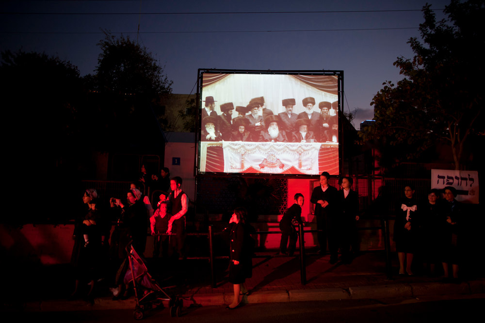 . Ultra-Orthodox Jews gather for a traditional Jewish wedding of the great-grandson of the Rabbi of the Sanz Hasidic dynasty followers, as a screen displays the men section of the wedding, in Netanya, Israel, Wednesday, Jan. 2, 2013. Thousands of people attended the wedding. (AP Photo/Oded Balilty)