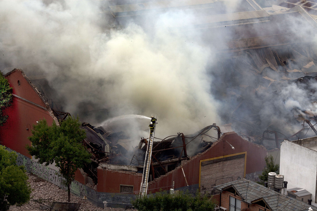 """. Aerial view of a fire at a warehouse in Barracas, in southern Buenos Aires, on February 5, 2014. At least nine firefighters and rescue workers were killed in Buenos Aires Wednesday when the wall of a warehouse engulfed by flames collapsed on top of them, officials said. Security Secretary Sergio Berni told reporters that several other first responders who were badly injured in the accident were \""""fighting for their lives.\"""" Officials said they do not know what caused the blaze in the 19th century era building, which was unoccupied at the time and housed archival bank records.  AFP PHOTO / NICOLAS Garcia/AFP/Getty Images"""