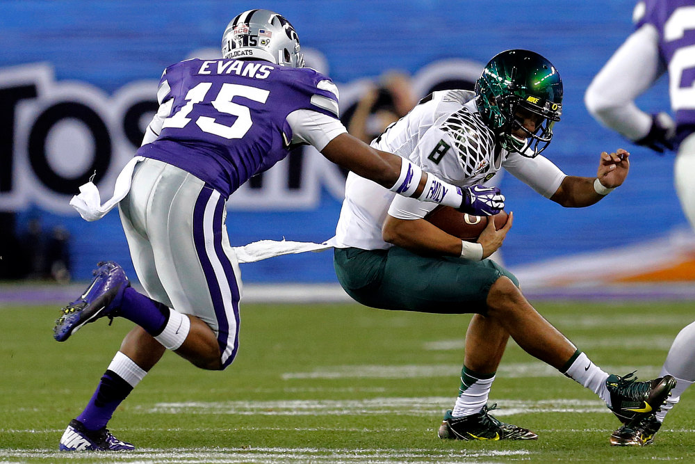 Description of . Oregon quarterback Marcus Mariota (8) tries to escape the reach of Kansas State defensive back Randall Evans (15) during the first half of the Fiesta Bowl NCAA college football game, Thursday, Jan. 3, 2013, in Glendale, Ariz. (AP Photo/Ross D. Franklin)