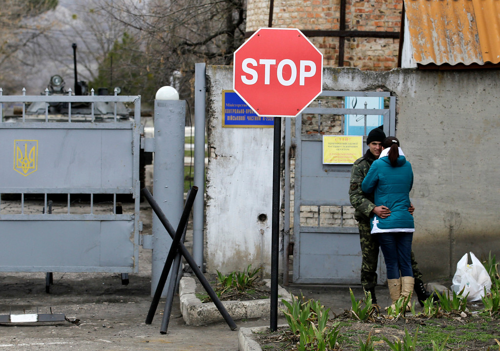 . A Ukrainian soldier kisses a woman outside the infantry  base as Russian soldiers surround the a Ukrainian military infantry base in Perevalne, Ukraine, Tuesday, March 4, 2014.  (AP Photo/Darko Vojinovic)