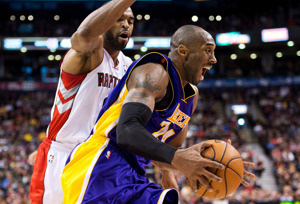 . Los Angeles Lakers guard Kobe Bryant, right, drives the net past Toronto Raptors Alan Anderson, left, during first half NBA basketball action in Toronto on Sunday Jan. 20, 2013. (AP Photo/THE CANADIAN PRESS,Nathan Denette)