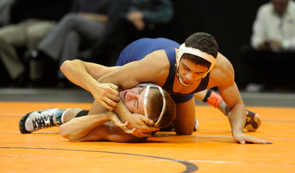 . DENVER, CO. - FEBRUARY 23: Pine Creek senior Geordan Martinez, top, wrapped up Pomona\'s Austin Marvel, bottom, during a class 5A, 138-pound championship match Saturday night. Martinez took the title, the first ever for Pine Creek. The CHSAA State Wrestling Tournament wrapped up, February 23, 2013, with final matches following the Parade of Champions at the Pepsi Center in downtown Denver. (Photo By Karl Gehring/The Denver Post)