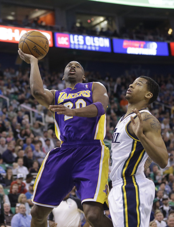 . Los Angeles Jodie Meeks (20) shoots as Utah Jazz\'s Trey Burke, right, looks on in the second quarter during an NBA basketball game Monday, April 14, 2014, in Salt Lake City, Utah. (AP Photo/Rick Bowmer)