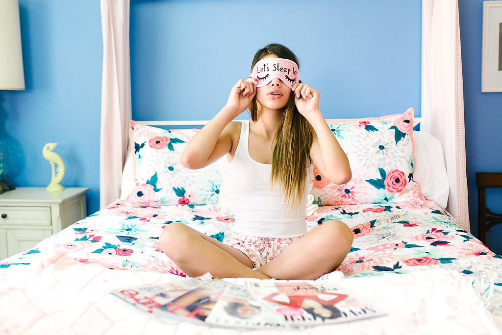 Lifestyle teen editorial shoot of Laneya Grace (JE Model) in a cute girly bedroom reading magazines, doing makeup, and eating donuts for breakfast by Tenley Clark Photography.