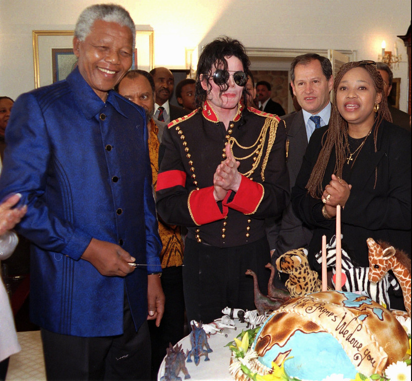""". American pop star Michael Jackson, center, applauds South African President Nelson Mandela, after singing \""""Happy Birthday\"""" to him at a private birthday function for the president at his Johannesburg home Thursday, July 18, 1996. Mandela\'s daughter Zinzi is seen at right. Jackson was on a four day trip to South Africa. (AP Photo/Sipiwe Mhlambi)"""