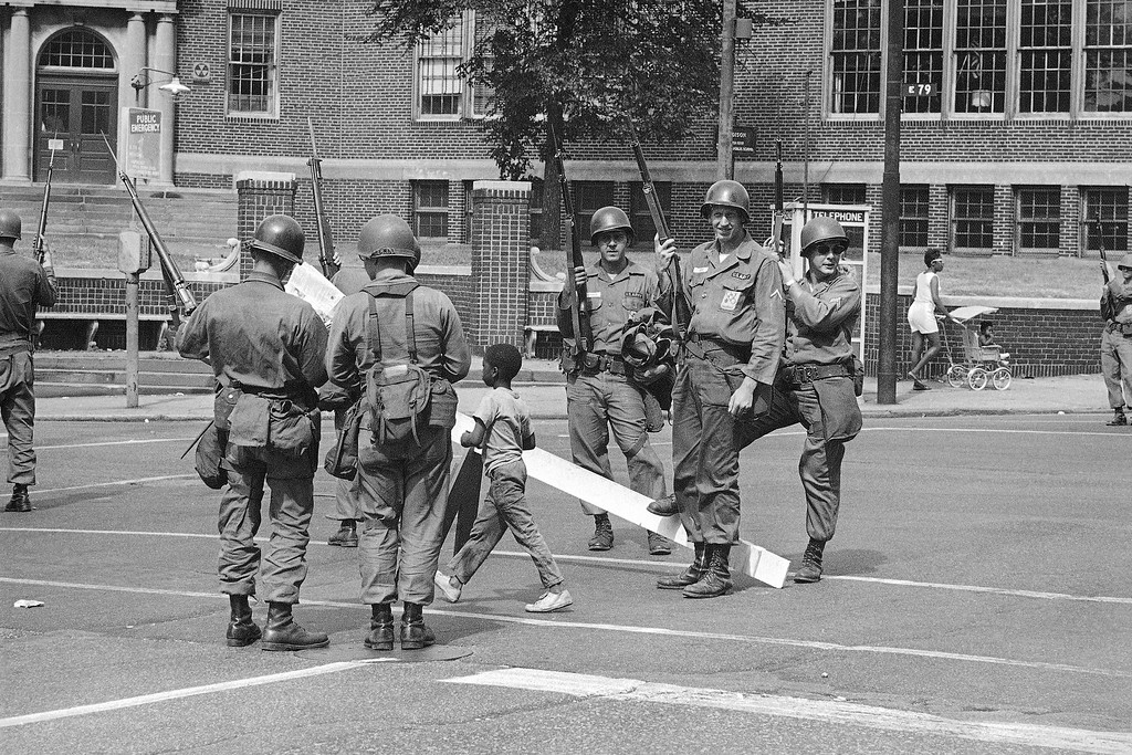 . A youngster strides straight and tall between the legs of National Guardsmen on duty in riot-torn section of Cleveland, July 22, 1966. Strife-weary city is girding itself for another possible night of vandalism and violence.  (AP Photo)