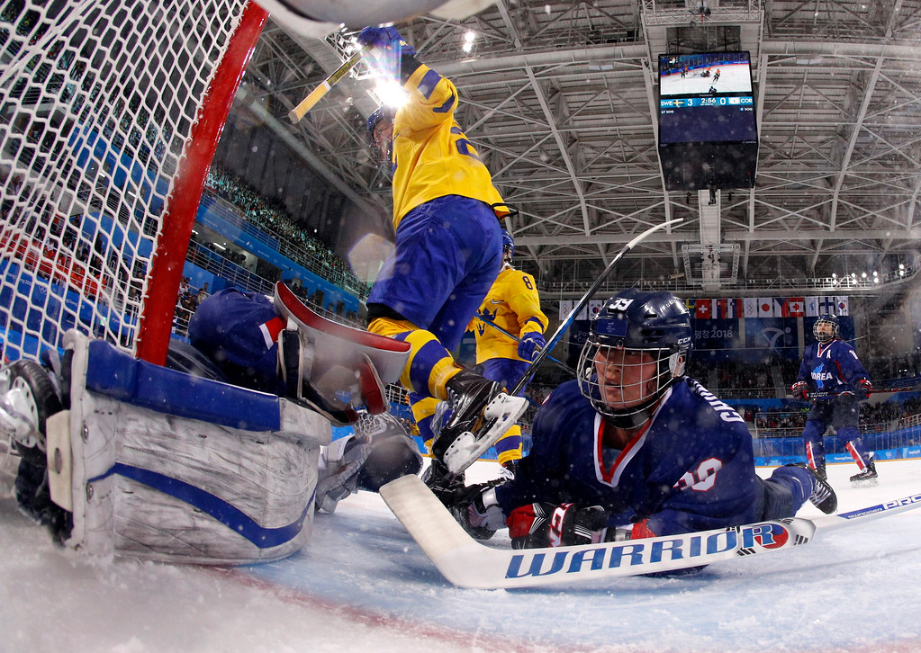 . North Korea\'s Hwang Chung Gum (39), of the combined Koreas team, falls into the goal during the first period of the preliminary round of the women\'s hockey game against Sweden at the 2018 Winter Olympics in Gangneung, South Korea, Monday, Feb. 12, 2018. (Kyung Hoon Kim/Pool Photo via AP)