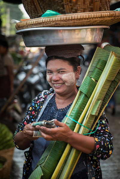 A street vendor counting her earnings at the food market in Mandalay.  Myanmar 2017