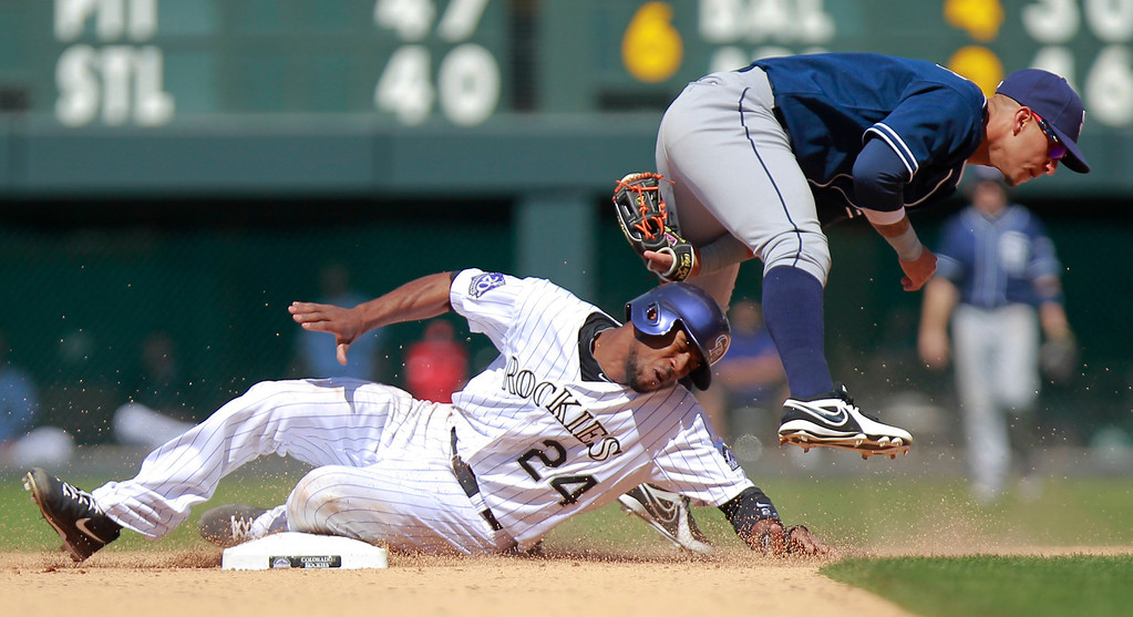 . San Diego Padres\' Jesus Guzman leaps over Colorado Rockies\' Dexter Fowler  as he steals second during the eighth inning of a baseball game Wednesday, Aug. 14, 2013 in Denver. Guzman dropped the ball when he landed. (AP Photo/Barry Gutierrez)