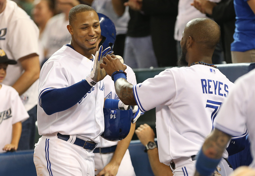 . TORONTO, CANADA - SEPTEMBER 11: Moises Sierra #14 of the Toronto Blue Jays is congratulated by Jose Reyes #7 after scoring a run in the fourth inning after hitting a triple during MLB game action against the Los Angeles Angels of Anaheim on September 11, 2013 at Rogers Centre in Toronto, Ontario, Canada. (Photo by Tom Szczerbowski/Getty Images)