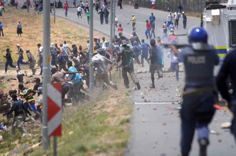 . Members of the South African Police Services fire rubber bullets at striking farmworkers during violent clashes, on January 10, 2012 in de Doorns, a small farming town about 140Km North of Cape Town, South Africa. The farm workers have said that they they will not return to work on the fruit growing region\'s farms until they receive a daily wage of at least R150($17) per day, which is about double what they currently earn. .  AFP PHOTO / RODGER  BOSCH/AFP/Getty Images