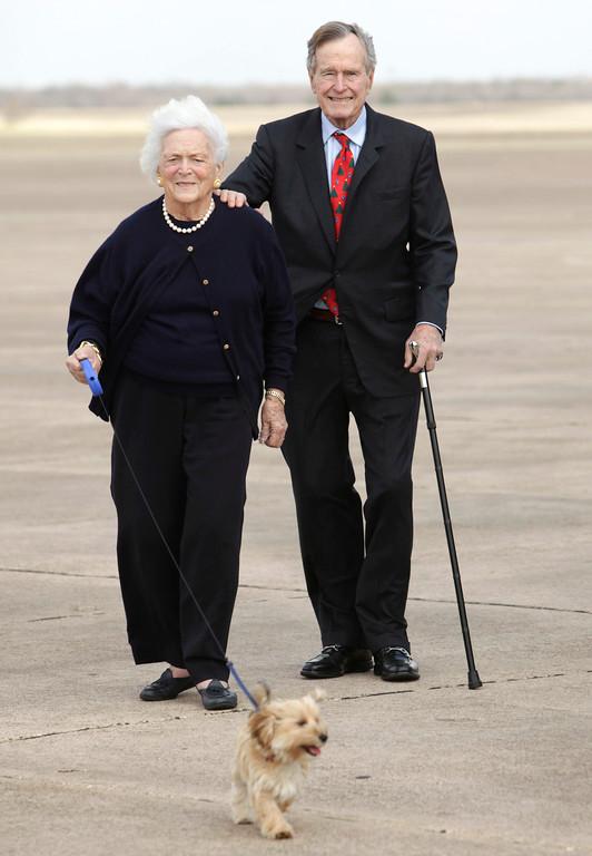 . Former President George H.W. Bush, right, and Barbara Bush walk their dog after arriving aboard Air Force One, Friday, Dec. 26, 2008 in Waco, Texas.  (AP Photo/Evan Vucci)