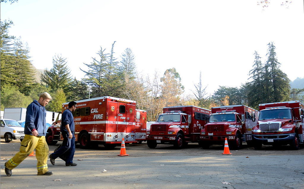 . Salinas Fire engineer Cappy Pottorff and Salinas figherfighter Gus Alvarez walk past a row of CAL Fire crew rigs as they prepare to return home after fighting the Pfeiffer Ridge Fire in Big Sur, Calif. on Thursday December 19, 2013. The pair had been on the fire with a Monterey area strike team since early Monday morning. (Photo David Royal/ Monterey County Herald)