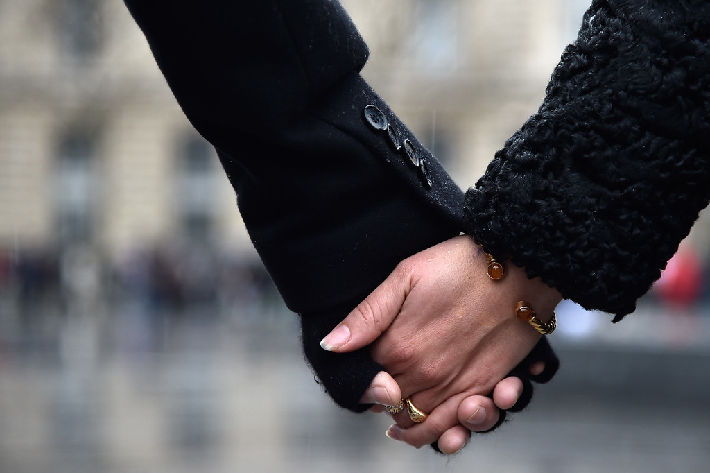 . People hold hands and form a circle around the Place de la Republique at midday in solidarity with victims of yesterday\'s terrorist attack on January 8, 2015 in Paris, France.  Twelve people were killed including two police officers as two gunmen opened fire at the offices of the French satirical publication Charlie Hebdo on January 7.  (Photo by Pascal Le Segretain/Getty Images)