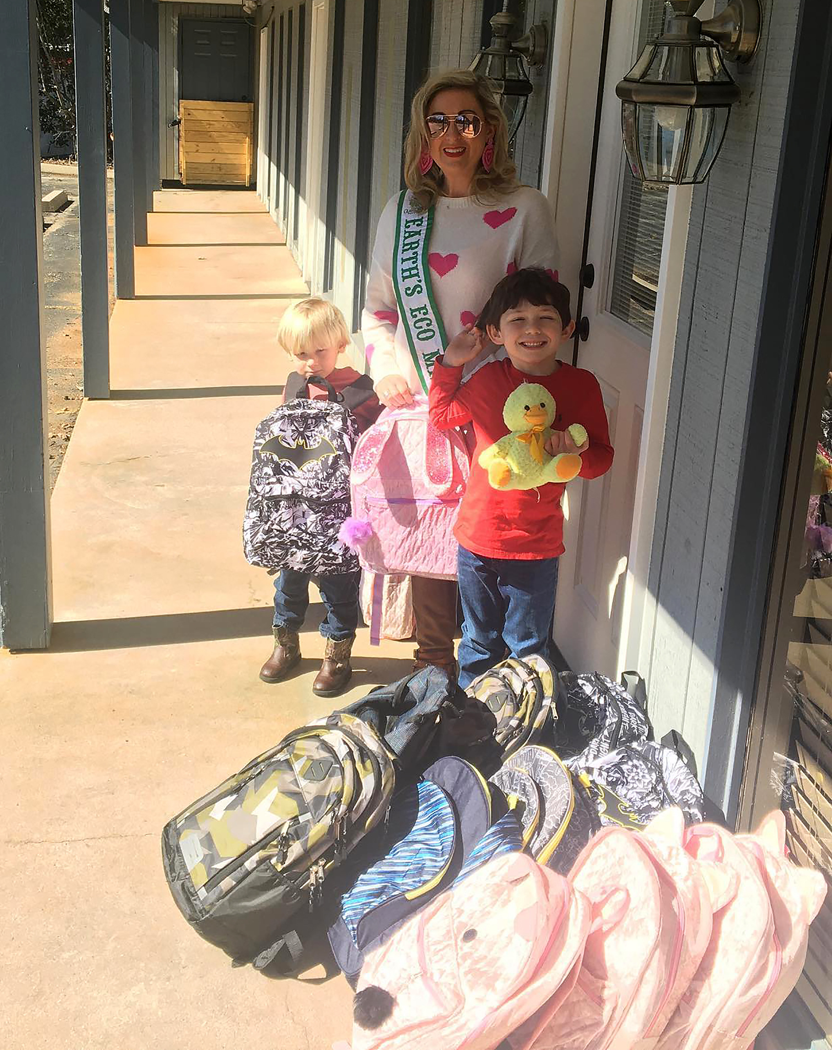 Allison and her two children Tucker (left) and Judson have knapsacks ready for local foster children.