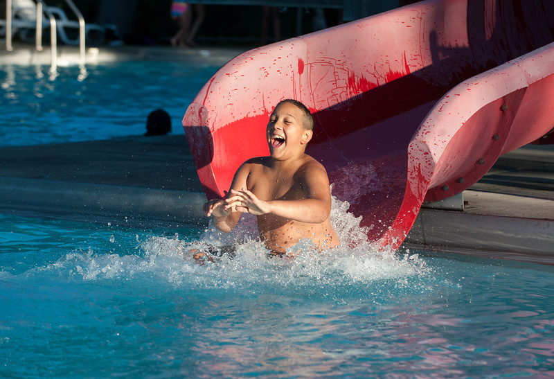 06/25/18  Wesley Bunnell | Staff  Emilio Morrison, age 13, is all smiles as he heads down the water slide at the Willow Brook Park Pool on Monday evening.