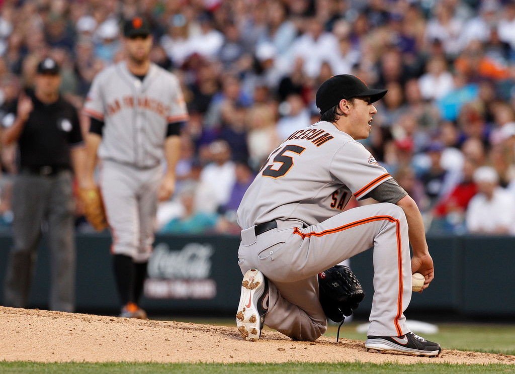 . San Francisco Giants starting pitcher Tim Lincecum, foreground, reacts after he lost his footing while winding up to throw a pitch and being called for a balk against the Colorado Rockies in the fourth inning of a baseball game in Denver, Saturday, May 18, 2013. (AP Photo/David Zalubowski)