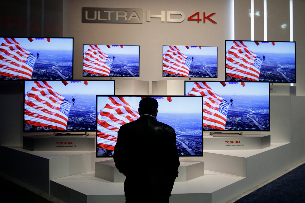 . A show attendee looks at the Ultra HD 4K displays at the Toshiba booth at the International Consumer Electronics Show on Thursday, Jan. 9, 2014, in Las Vegas. (AP Photo/Jae C. Hong)
