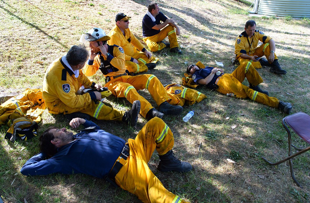""". Firefighters take a break after back burning near Mount Victoria in the Blue Mountains on October 21, 2013, as volunteer fire brigades race to tame an enormous blaze, with officials warning it could merge with others to create a \""""mega-fire\"""" if weather conditions worsen.   AFP PHOTO/William WEST/AFP/Getty Images"""