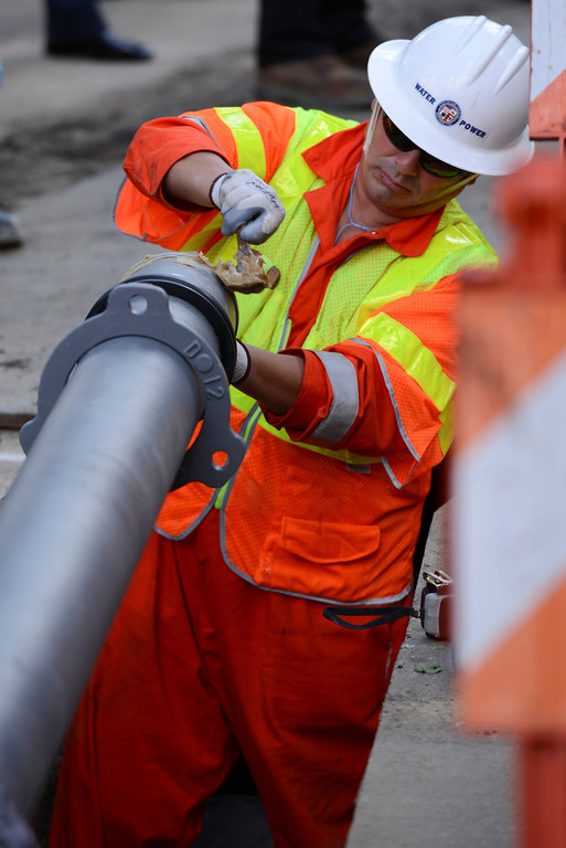 . A DWP employee spreads a sealer around the end of an earthquake proof water pipe along Contour Drive in Sherman Oaks.  The new pipe, made in Japan, has withstood magnitude 9 earthquakes.  The secret to the new pipes lies in a new type of flexible rubberized joints.   Photo by David Crane/Staff Photographer