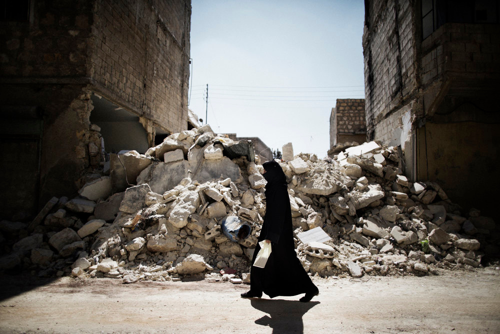 Description of . A Syrian woman walks past a destroyed building while reaching a food distribution centre in Aleppo on September 13, 2012. Syrian fighter jets and tanks pounded the northern city of Aleppo, an AFP journalist said, as witnesses reported rebels advancing into the key contested central Midan district. MARCO LONGARI/AFP/Getty Images