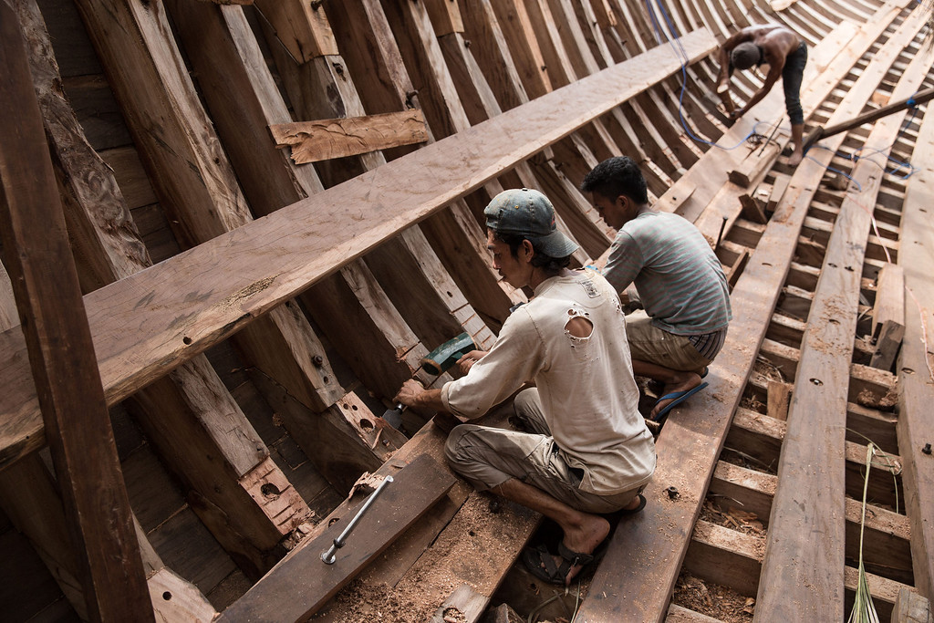 . Buginese men work as they prepare to install a wooden block in the hull of phinisi at Tanjung Bira Beach on May 2, 2014 in Bulukumba, South Sulawesi, Indonesia.  (Photo by Agung Parameswara/Getty Images)