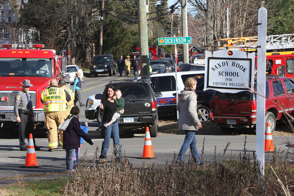 . Parents walk away from the Sandy Hook  Elementary School with their children following a shooting, Friday, Dec. 14, 2012 in Newtown, Conn. A man opened fire inside the Connecticut elementary school where his mother worked Friday, killing 26 people, including 18 children, and forcing students to cower in classrooms and then flee with the help of teachers and police. (AP Photo/The Journal News, Frank Becerra Jr.)