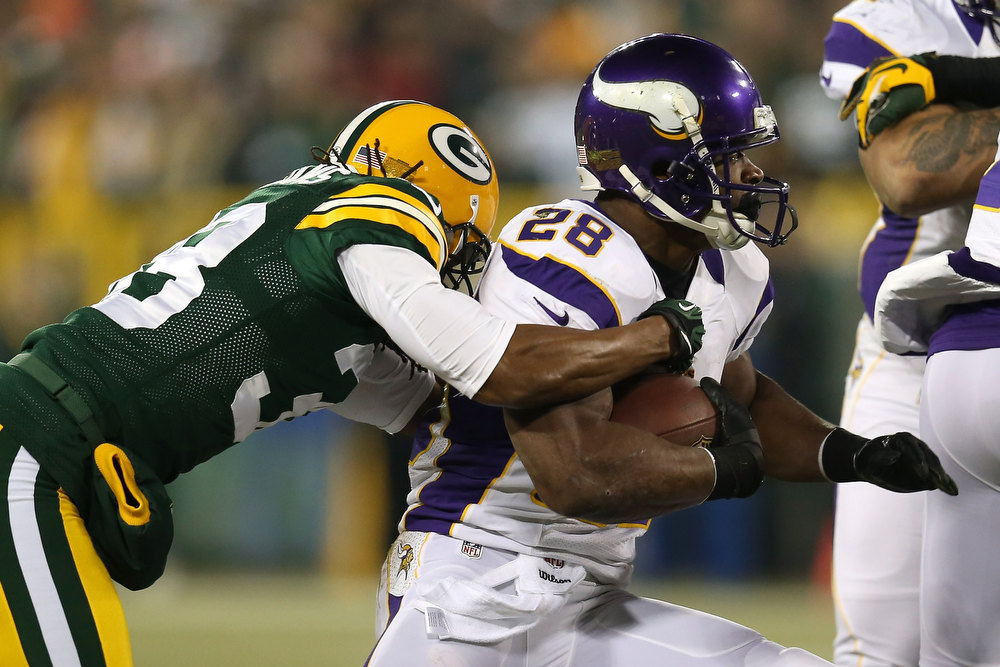 Description of . Running back Adrian Peterson #28 of the Minnesota Vikings runs the ball as he is hit by cornerback Tramon Williams #38 of the Green Bay Packers in the first quarter during the NFC Wild Card Playoff game at Lambeau Field on January 5, 2013 in Green Bay, Wisconsin.  (Photo by Jonathan Daniel/Getty Images)