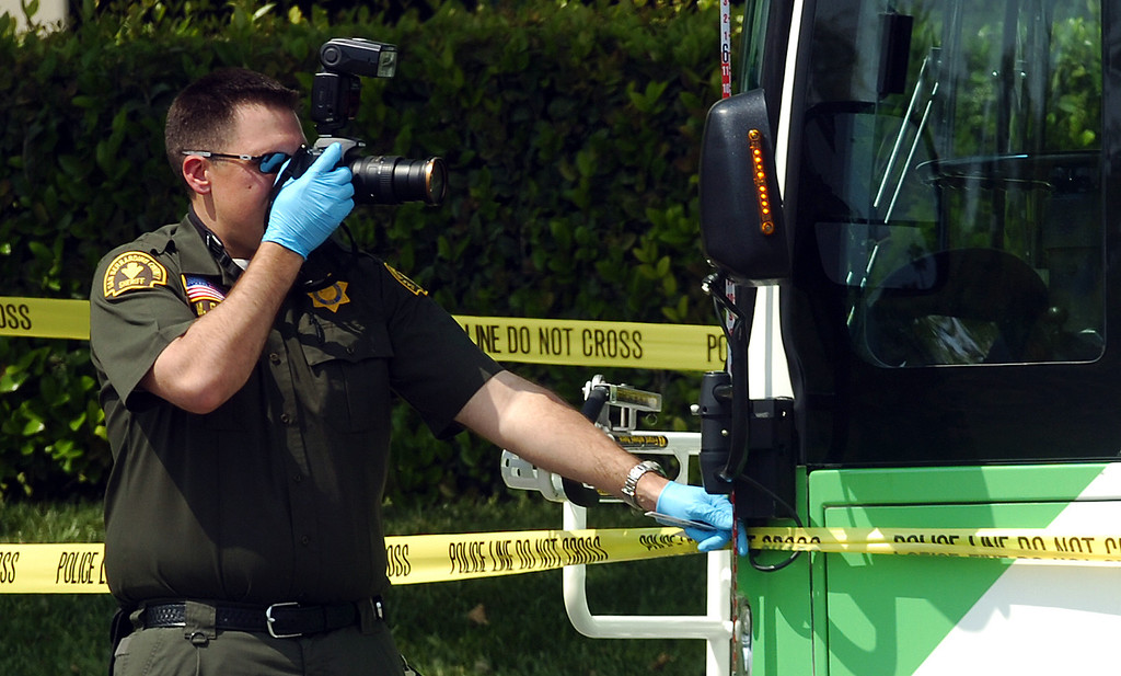 . Mike Russ, a San Bernardino Sheriff\'s crime scene investigator, takes photos of an OmniTrans bus that was struck by gunfire during an officer involved shooting in San Bernardino May 9, 2013. Two suspects in a Yucca Valley homicide led authorities on a high-speed chase Thursday that ended with a gun battle, one suspect dead, another wounded and a California Highway Patrol officer wounded. The CHP didn\'t say where the bullet struck the officer, but said the wound was not life-threatening. (Rick Sforza/The Sun, San Bernardino)