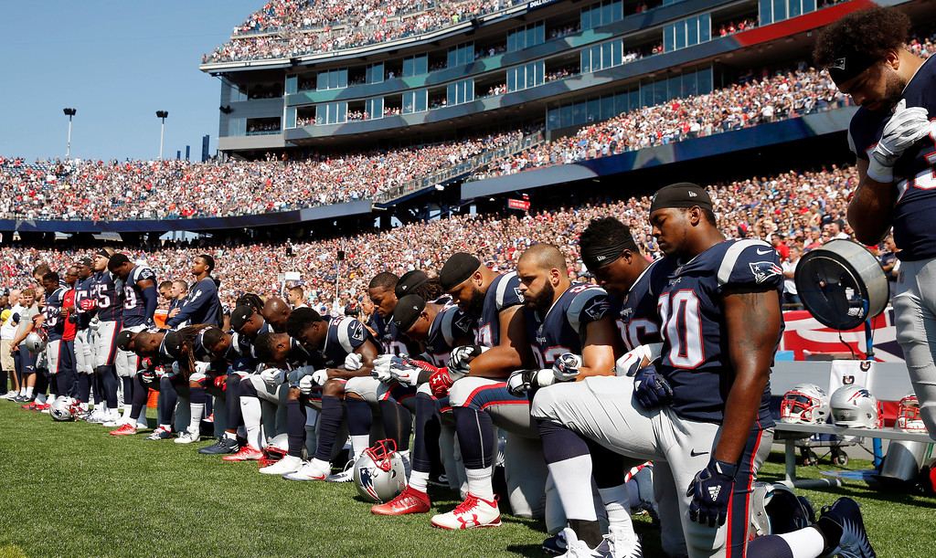 . Several New England Patriots players kneel during the national anthem before an NFL football game against the Houston Texans, Sunday, Sept. 24, 2017, in Foxborough, Mass. (AP Photo/Michael Dwyer)