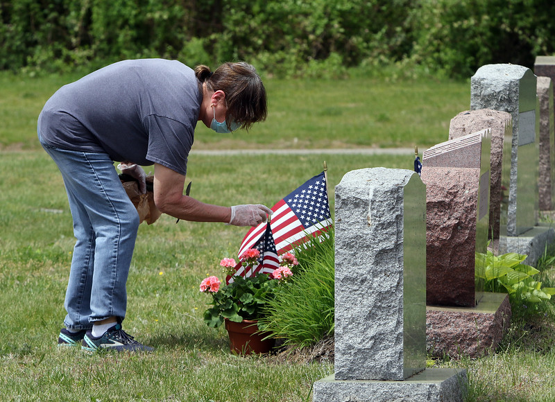 Fox Hill Cemetery in Billerica, on Saturday of Memorial Day weekend. Jo Ann Bushong of Hudson, N.H., puts an arrangement on the grave of her parents, Robert & Dorothy Fleming.  (SUN/Julia Malakie)