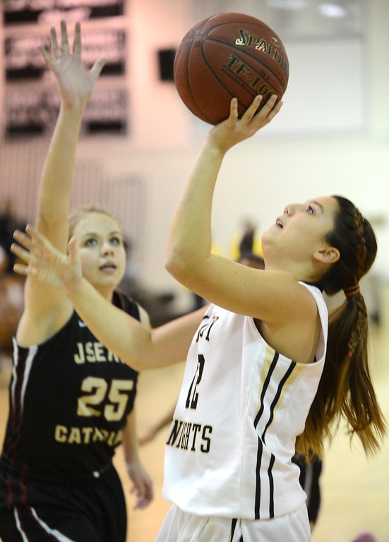 . Bishop Montgomery\'s Christine Delapina (12) shoots around JSerra\'s Megan House (25) in a CIF Division IV-AA quarterfinal game Wednesday night in Torrance. 20130220 Photo by Steve McCrank / Staff Photographer
