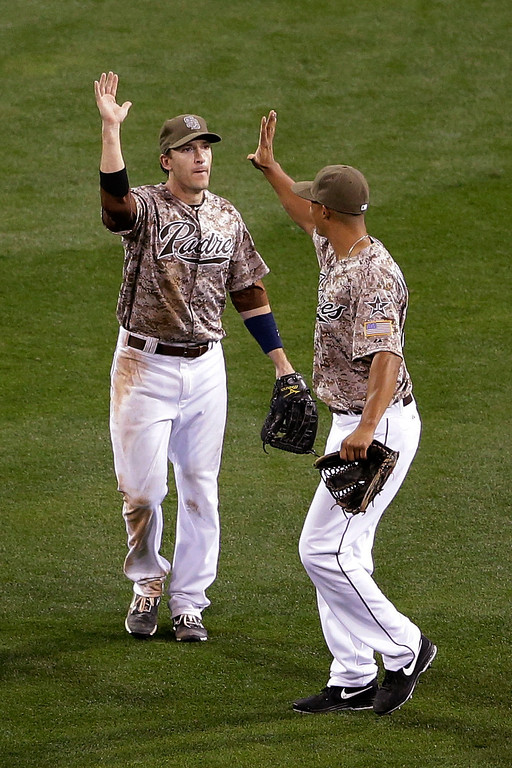 . San Diego Padres outfielder Chris Denorfia, left, celebrates with teammate outfielder Will Venable after beating the Los Angeles Dodgers in an opening night baseball game on Sunday, March 30, 2014, in San Diego. The Padres won, 3-1. (AP Photo/Gregory Bull)