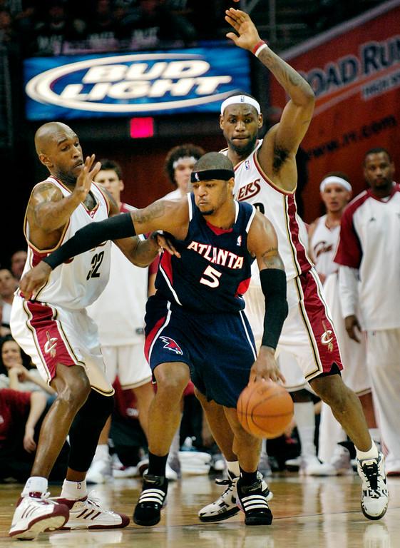 . Jeff Forman/JForman@News-Herald.com Joe Smith and LeBron James defend Hawks forward Josh Smith Tuesday at Quicken Loans Arena.