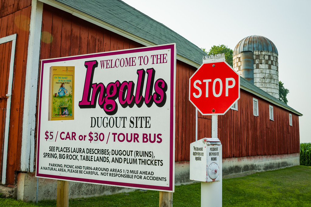 A sign in front of a modern red barn and silo reads, 'Welcome to the Ingalls Dugout Site, $5/car or $30/tour bus'.