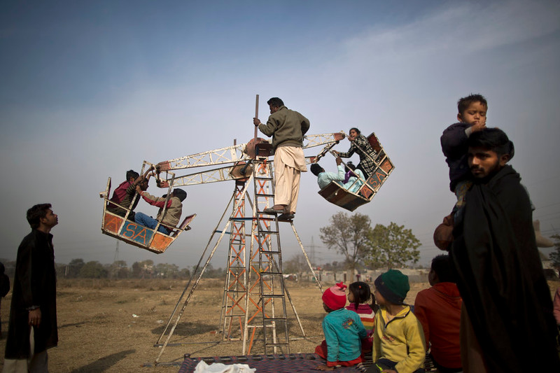 . Pakistani Christian children enjoy a ride on a hand-operated Ferris wheel for the price of 10 rupees, (10 U.S. cents), at a makeshift entertainment park set up in a slum that hosts Christian families, in preparation for the Christmas holiday on the outskirts of Islamabad, Pakistan, Wednesday, Dec. 24, 2014. (AP Photo/Muhammed Muheisen)
