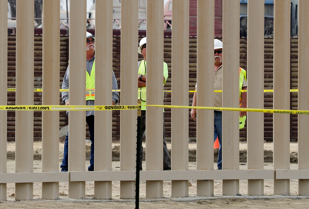 . Crews look through a border wall prototype near the border with Tijuana, Mexico, Thursday, Oct. 19, 2017, in San Diego. Companies are nearing an Oct. 26 deadline to finish building eight prototypes of President Donald Trump\'s proposed border wall with Mexico. (AP Photo/Gregory Bull)
