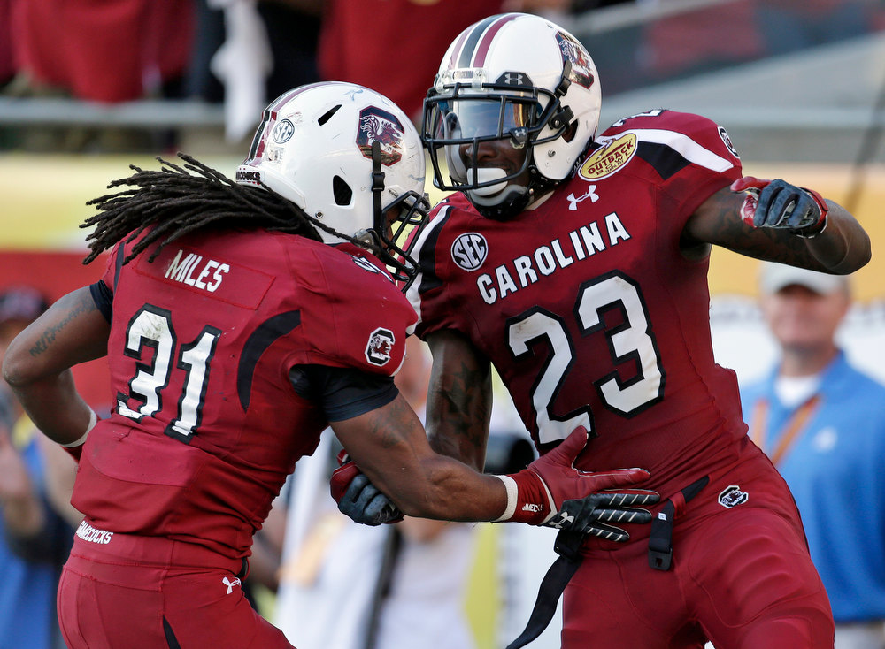 Description of . South Carolina wide receiver Bruce Ellington (23) celebrates with teammate Kenny Miles (31) after scoring on a 32-yard touchdown reception during the second half of the Outback Bowl NCAA college football game against Michigan, Tuesday, Jan. 1, 2013, in Tampa, Fla. South Carolina won 33-28. (AP Photo/Chris O'Meara)