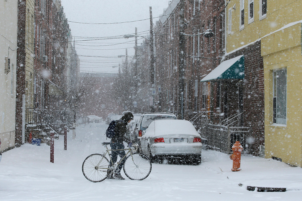 . A pedestrian pushes his bicycle through a snow storm, Tuesday, Jan. 21, 2014, in south Philadelphia. A storm is sweeping across the Mid-Atlantic and New England. (AP Photo/Matt Slocum)