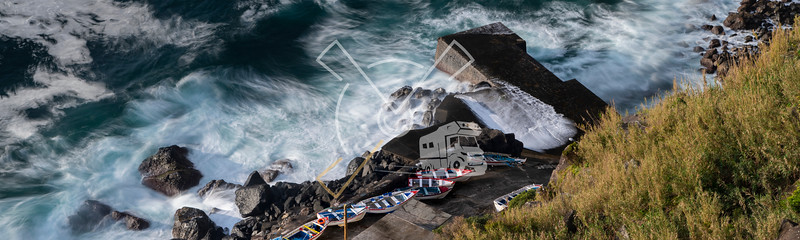 A wild sea hitting the scenic Porto Pesqueiro/fishing port of Arnel with its colorful fishing boats.