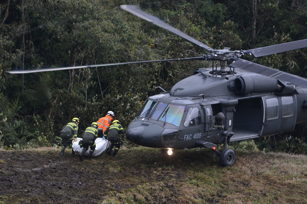 . Rescue workers place the body an airplane crash victim into a waiting helicopter, in La Union, near Medellin, Colombia, Tuesday, Nov. 29, 2016. The chartered plane was carrying a Brazilian soccer team to the biggest match of its history when it crashed into a Colombian hillside and broke into pieces, killing 75 people and leaving six survivors, Colombian officials said Tuesday. (AP Photo/Luis Benavides)
