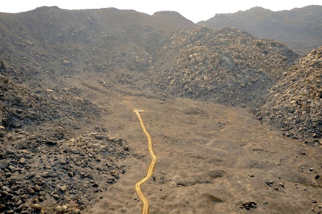 . This Thursday, July 4, 2013, aerial photo provided by Prescott Fire Department, shows the site where 19 firefighters were killed in an Arizona wildfire on Sunday, June 30, 2013. The line in the middle of the photo, built by a bulldozer after the deaths, allowed law enforcement and fellow firefighters to reach the fallen firefighters and remove their bodies from the mountain the day after they were killed. The Prescott Fire Department identified the site where the men died as the discolored patch of earth just beyond where the bulldozer line ends. The photo also shows that the intense wildfire wiped out all vegetation in the area. (AP Photo/Prescott Fire Department)