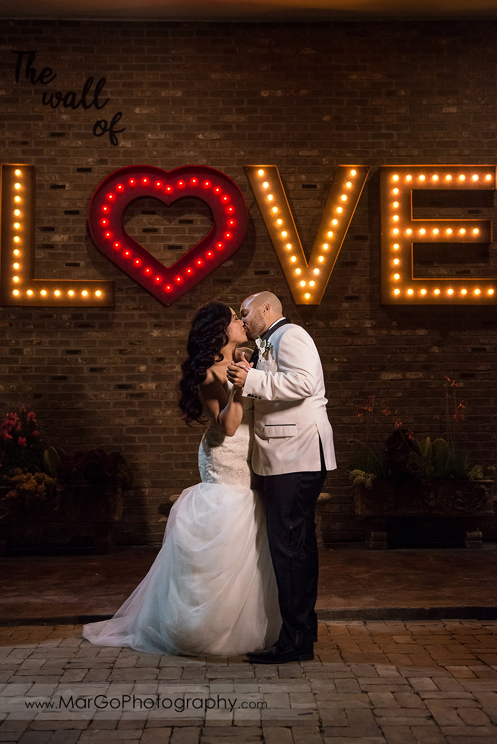 bride and groom kissing under LOVE sign at Sunol's Casa Bella