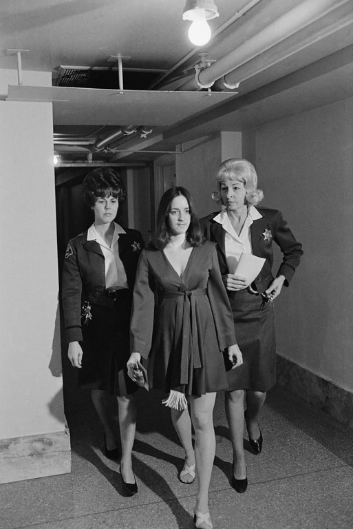 . Susan Atkins, appearing cheerful and wearing a low-cut dress, is escorted by sheriff\'s deputies to a court appearance, Feb. 4, 1970 in Los Angeles. She and other alleged members of the Charles Manson hippie clan are accused of seven murders, including that of actress Sharon Tate.  Ms. Atkins was successful in winning a delay in start of her trial until March. (AP Photo)