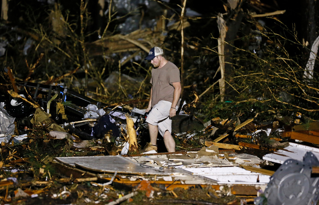. A volunteer searches the remains of several mobile homes in Louisville, Miss., early Tuesday morning, April 29, 2014 after a tornado hit the east Mississippi community Monday.  (AP Photo/Rogelio V. Solis)