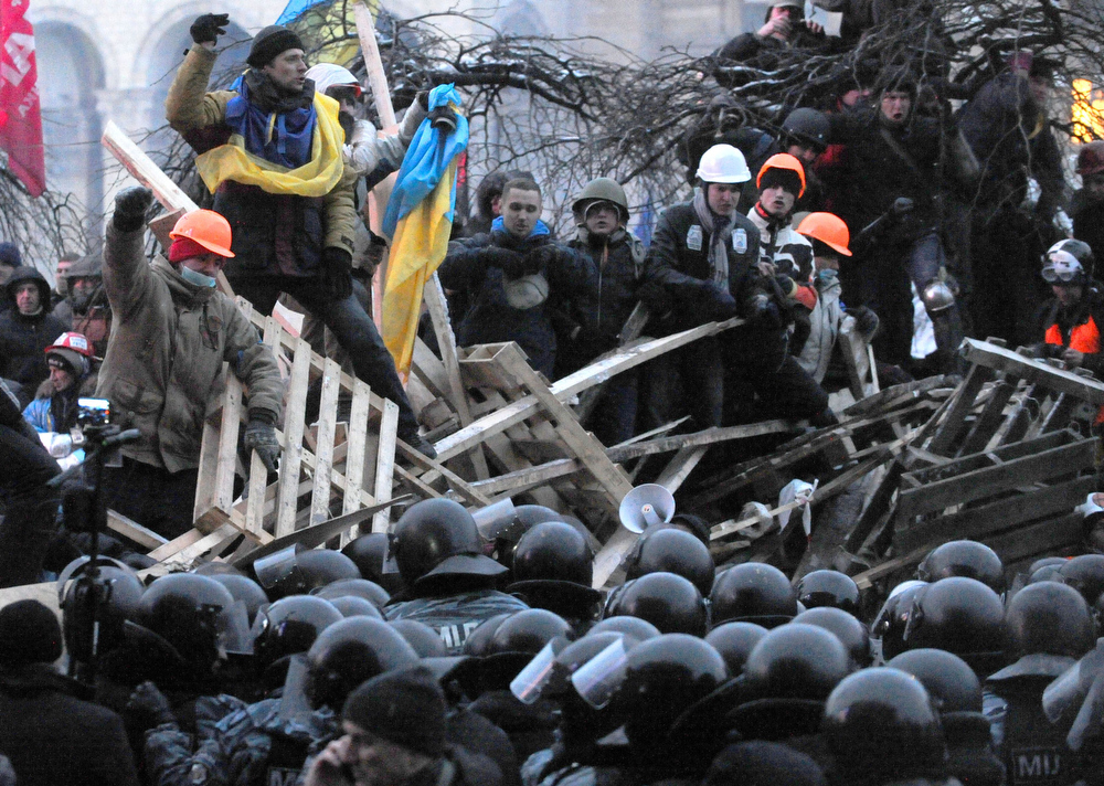 . Anti-Yanukovych protesters defend their barricades in front of anti-riot police on Independence Square in Kiev, early on December 11, 2013. Ukrainian security forces pulled out of the epicentre of mass protests in Kiev today after a nine hour standoff with thousands of demonstrators, in a major boost for the opposition to President Viktor Yanukovych.VIKTOR DRACHEV/AFP/Getty Images