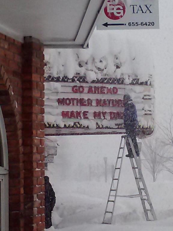 . This photo provided by Laurie Cullen, a worker sends a message about the snow on the marquis of the Aurora Theater in East Aurora, N.Y. , on Thursday, Nov. 20, 2014.  A  new blast of lake-effect snow roared through western New York with thunder and lightning on Thursday, raising to nearly 6 feet the three-day total in parts of the Buffalo area. (AP Photo/Courtesy of Laurie Cullen)